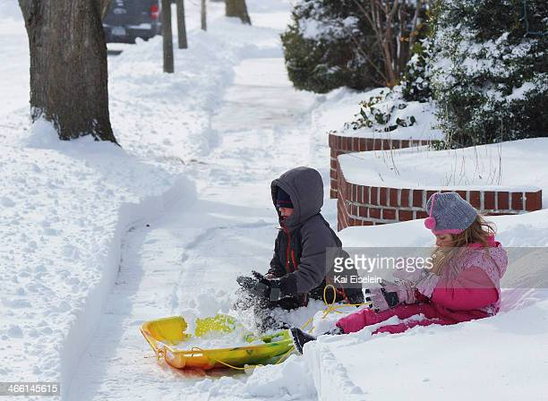 CONTENT] Children fill a plastic sled with snow after a blizzard in Massapequa New York