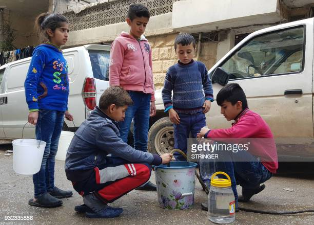 TOPSHOT Children fill up containers with water in the Syrian Kurdish city of Afrin on March 15 2018 as people are preparing for the possibility of a...