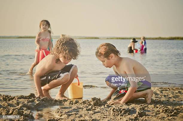Children filling buckets and playing in sand at the beach.