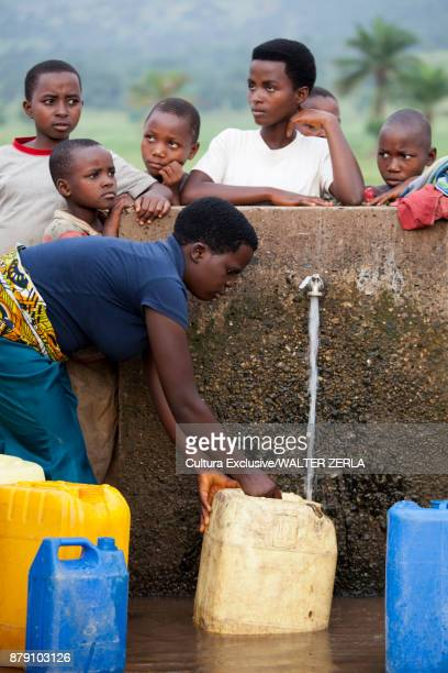 Children filling containers at community water pump, Masango, Cibitoke, Burundi, Africa