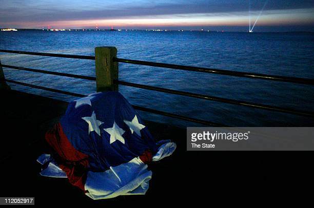 Children find shelter under a replica of the first Confederate flag as they look out to Fort Sumter from the Battery in downtown Charleston South...