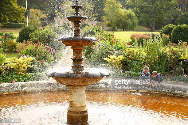 Children fish for coins with sticks from the fountain in the Government Gardens of the Port Arthur Historical Site on April 18 2016 in Port Arthur...