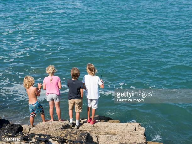 Children fishing from the breakwater Bude Cornwall UK