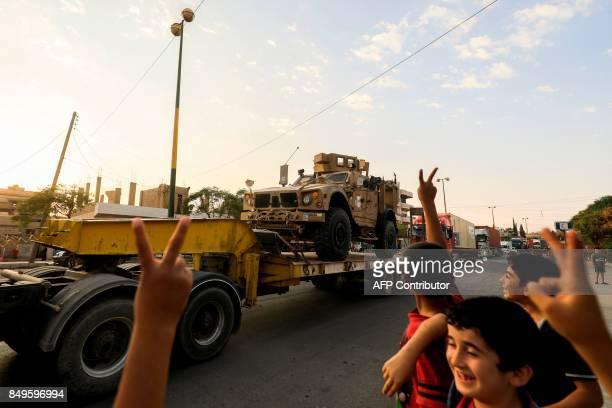 Children flash the victory gesture as a military convoy carrying US-made Oshkosh armoured vehicles, bulldozers, and arms headed for Syrian Democratic...