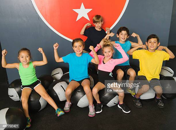 Children flexing their muscles in gym