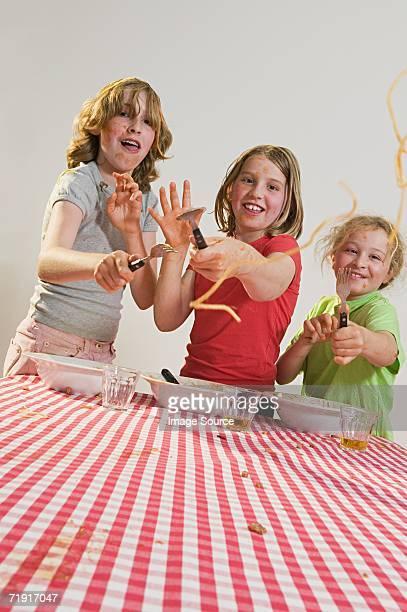 Children flicking spaghetti