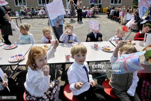 Children fly their handmade Union flags at the Bucklebury Church of England Primary School Royal wedding party in the school playground
