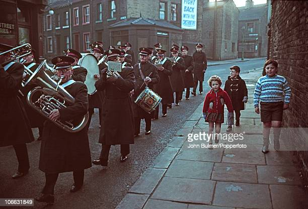 Children follow a Salvation Army band playing on a street in Halifax West Yorkshire in 1965