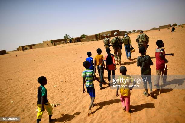Children follow soldiers of the Bundeswehr the German Armed Forces after leaving a weekly cattle market on the outskirts of Gao on March 7 2017 in...