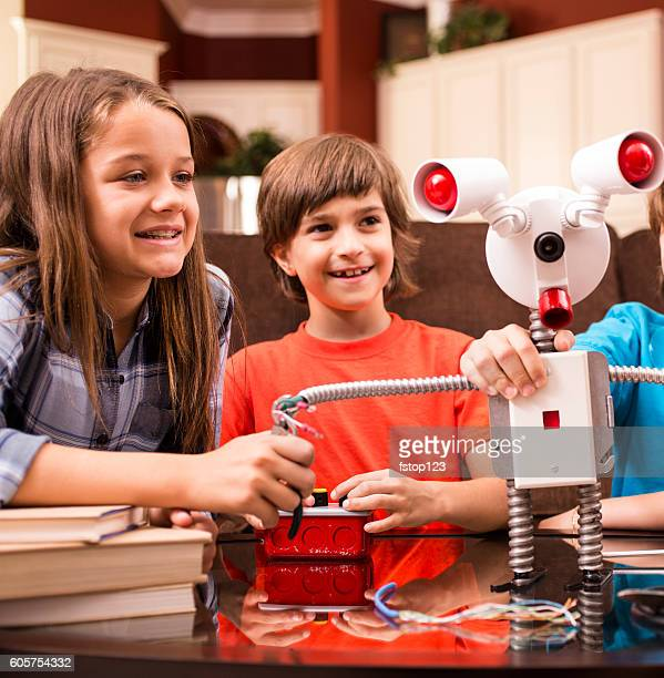 Children friends build robot together at home.
