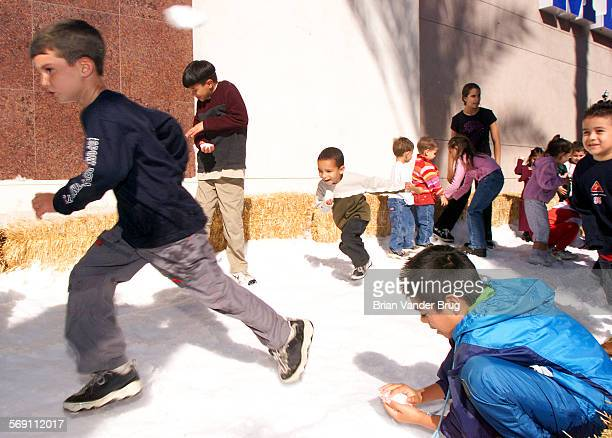 Children frolick in the snow at Media City Center in Burbank Friday morning November 23 2001 after 15 tons of ice was shaved and blown onto the site...