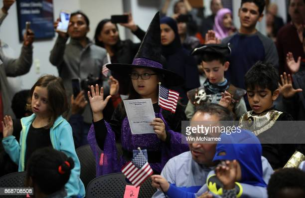 Children from 22 countries take the oath of US citizenship during a Halloweenthemed citizenship ceremony October 31 2017 in Fairfax Virginia...