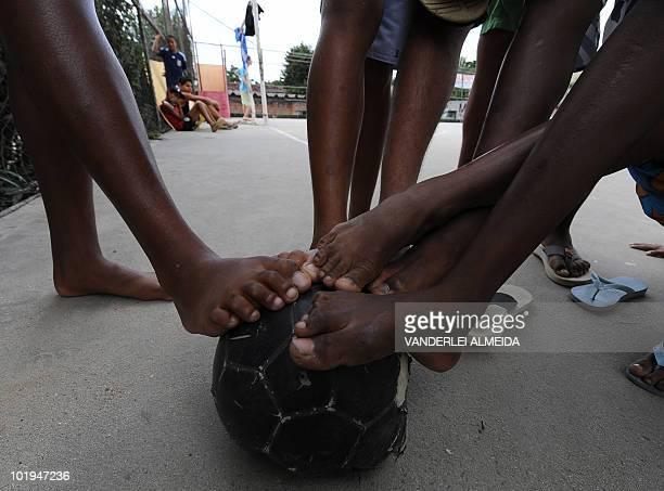 Children from a neighborhood of Rio de Janeiro play football on June 3 2010 AFP PHOTO/VANDERLEI ALMEIDA
