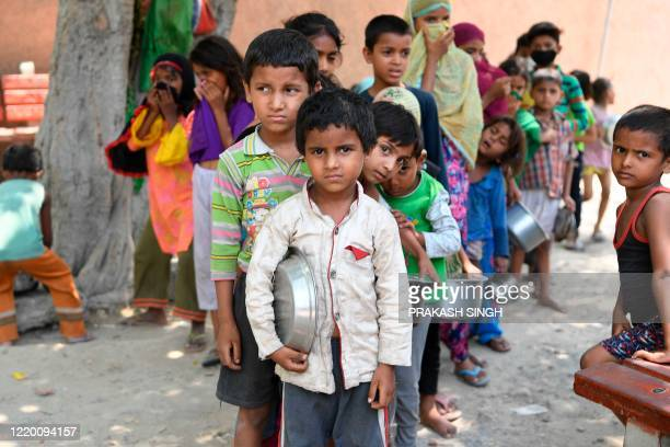 Children from a slum stand in queue to get free food after the government eased a nationwide lockdown as a preventive measure against the COVID-19...