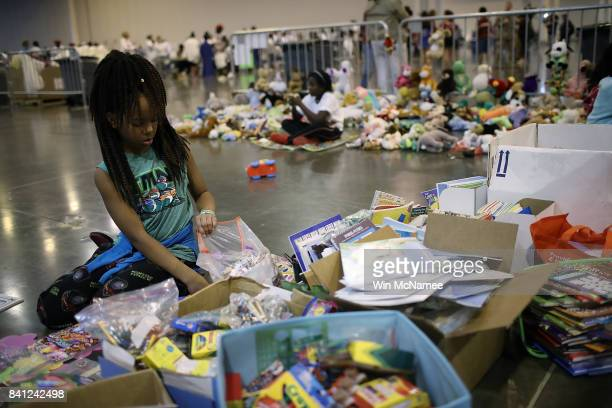 Children from families forced from their homes due to flooding play with donated toys at the NRG Center August 31, 2017 in Houston, Texas. Thousands...