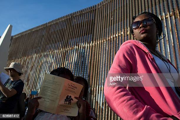 Children from Haiti seeking for asylum in the US, stand next to the border fence with the US, in Playas de Tijuana, in northwestern Mexico on...
