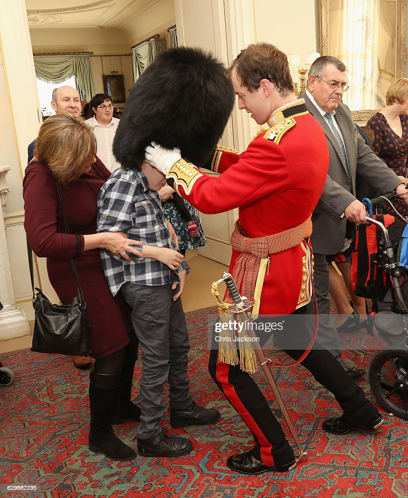 Children from Helen and Douglas House try on Captain Matthew Wright of the Welsh Guards bearskin hat during a reception at Clarence House for children from Helen and Douglas House on December 14, 2016 in London, England. The Duchess of Cornwall, Patron, Helen & Douglas House invited children from the charity and children supported by Roald Dahl's Marvellous Children's Charity to decorate the Christmas tree and join Her Royal Highness for lunch at Clarence House.