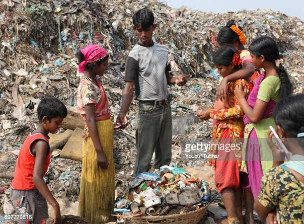 Children from indigent community selling useable things to a boy at garbage pile in Matual dumping yard Demra Dhaka Bangladesh November 2009 Children...