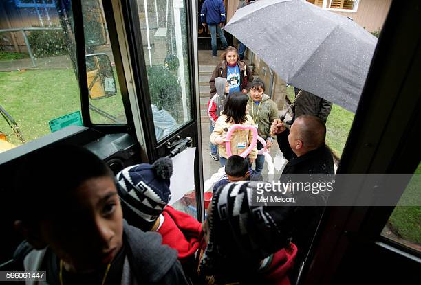 Children from Latona Elementary School in Lincoln Heights file into the bus as they leave the Grace Simons Lodge in Los Angeles on December 7 unable...