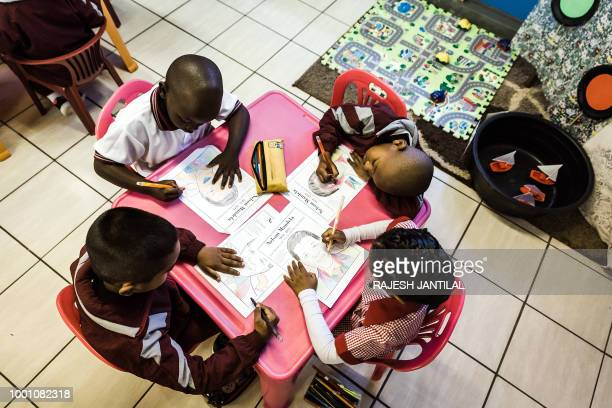 Children from Northlen Primary school colour in posters to commemorate the life of former South African President Nelson Mandela in Durban on July 18...