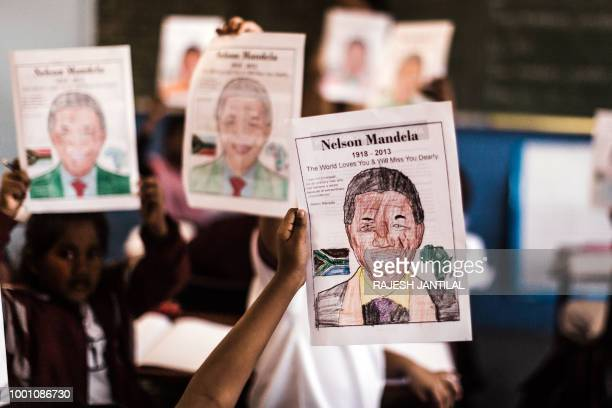 Children from Northlen Primary school hold up their posters of former South African President Nelson Mandela in Durban on July 18 2018 July 18 marks...