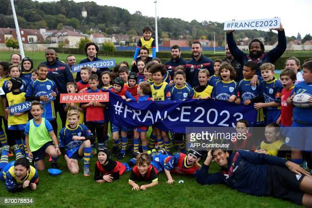 Children from Pontlieu rugby club pose with French rugby players and hold banners and placards refering to France's bid to host the 2023 Rugby World...