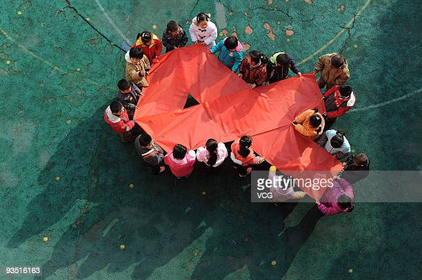 Children from Shuanggang Kindergarten hold a giant 'Red Ribbon' to mark World AIDS day on November 30 2009 in Hefei Anhui Province of China...
