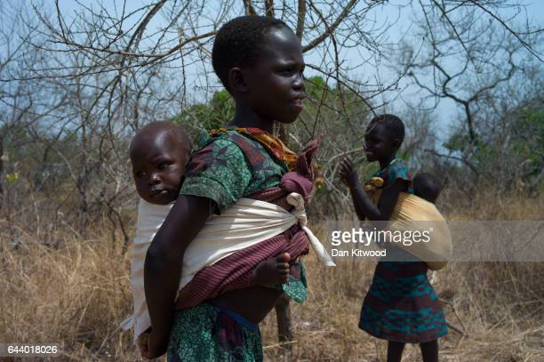 Children from South Sudan stand in scrub near the Bidi Bidi refugee camp on February 22, 2017 in Arua, Uganda. The continued flow of refugees from...