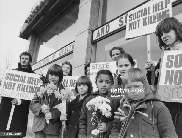 Children from St George's Roman Catholic School holding small bunches of flowers stand before a group of adults holding placards reading 'Social help...