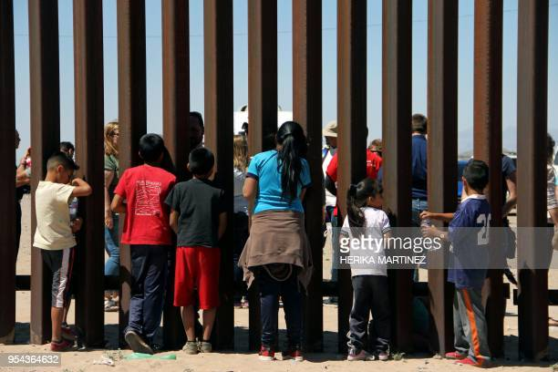 Children from the Anapra area observe a binational prayer performed by a group of religious presbyters on the border wall between Ciudad Juarez...