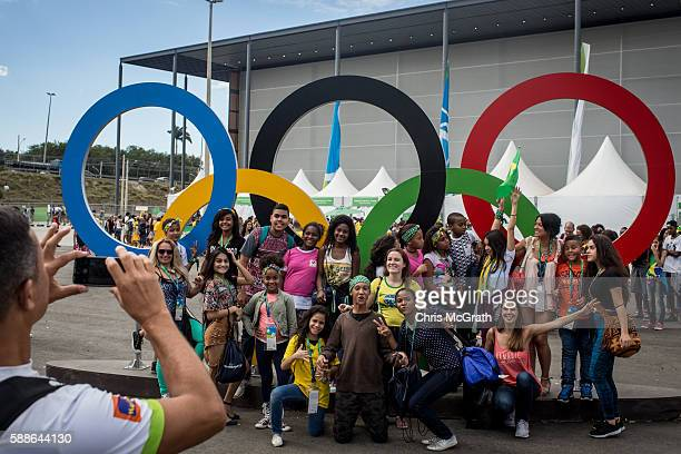 Children from the Cantagalo 'favela' community pose for a photograph with the Olympic rings at the Olympic Rugby 7's venue on August 11 2016 in Rio...
