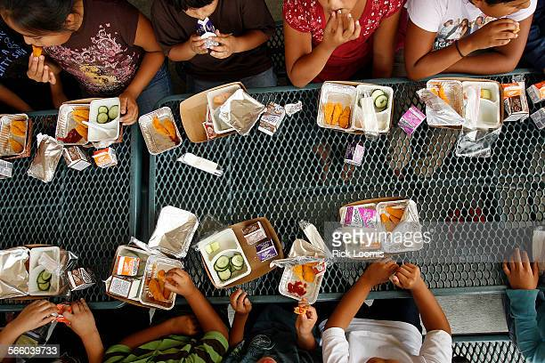 Children from the Cesar Chavez Elementary school eat lunch on a day when Los Angeles Unified Superintendent David Brewer and Kevin Regan of the City...