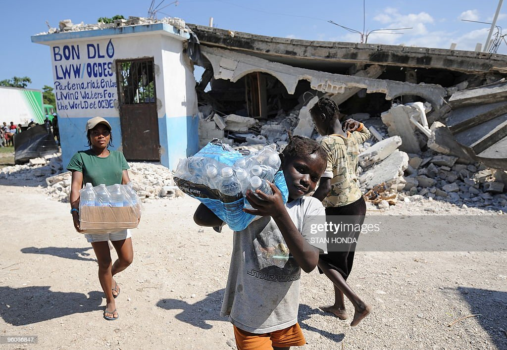 Children from the Chirstian Orphanage of Bonne Nouvelle carry water distributed by a Sri Lankan United Nations unit January 23, 2010 in Leogane, Haiti. The Sri Lankans handed out food and water donated by the US for earthquake relief. AFP PHOTO/Stan Honda