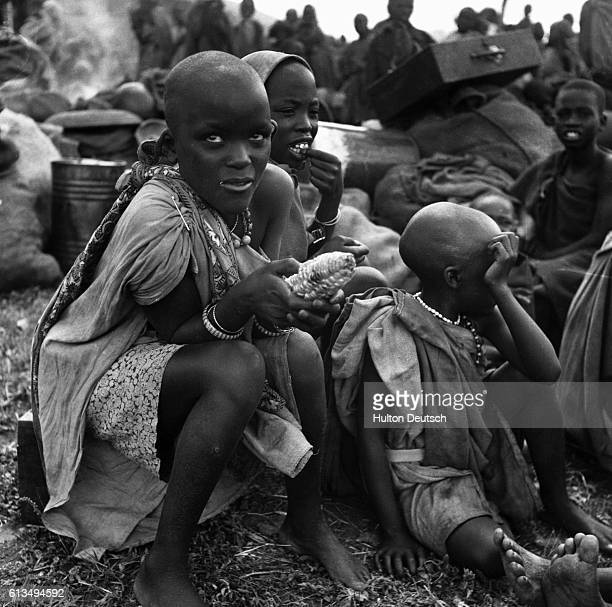 Children from the Kikuyu tribe eat a meal while being detained with their families in a prison camp in the aftermath of the Mau Mau rebellion in...
