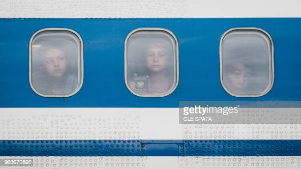 TOPSHOT Children from the region around Chernobyl in the Ukraine look out of the window of a plane after arriving at the airport in Hanover central...