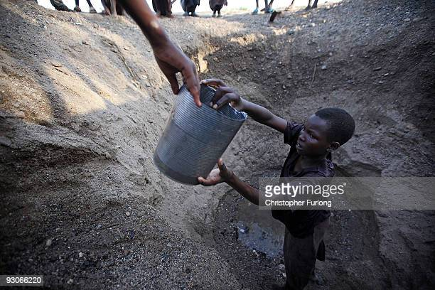 Children from the remote Turkana tribe in Northern Kenya dig a hole in a river bed to retrieve water As water levels dwindle many children are killed...