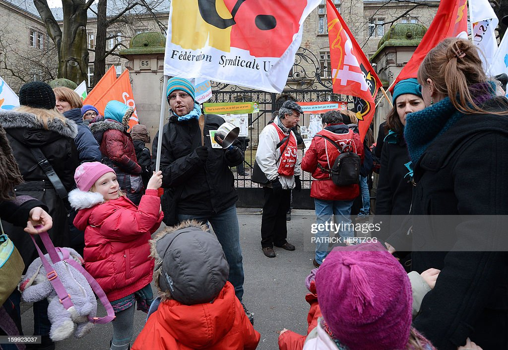 Children gather alongside adults in front of the headquarters of the local office of the Education department, on January 23, 2013, in Strasbourg, eastern France, as they take part in a nationwide strike and protest action against a proposed reform to increase the class time of primary school students. Around 100 people gathered in Strasbourg as several hundred other teachers gathered at protest rallies in various cities across the country.