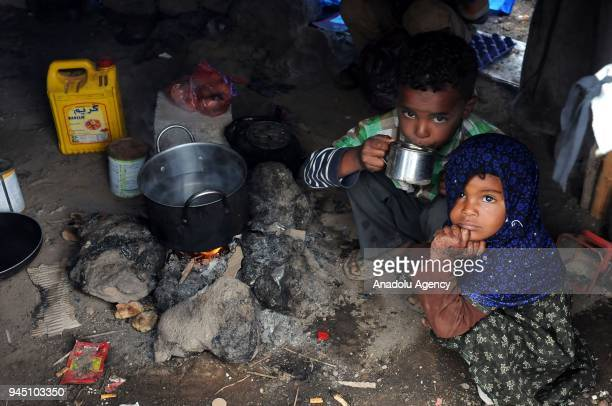 Children gather around a cooking fire at Darwan refugee camp in Amran north of Sanaa Yemen on April 11 2018 Yemeni families displaced by the clashes...