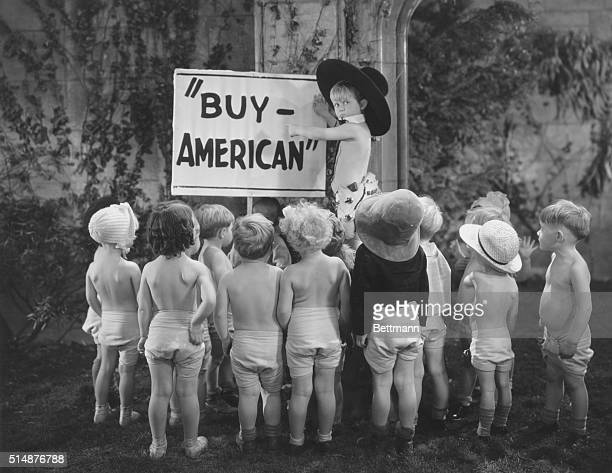 Children gather around a sign reading Buy American in a scene from Polly Tix in Washington one of the Baby Burlesk series of shorts that featured...