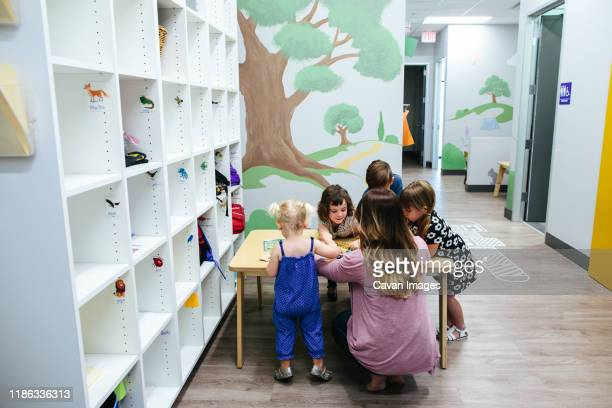 children gather at a table with teacher in educational facility - calabasas stock pictures, royalty-free photos & images