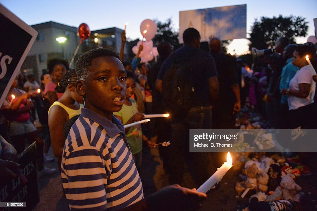 Children gather at the Michael Brown Jr. memorial on Canfield Drive during a candlelight vigil held in honor of Jamyla Bolden on August 20, 2015 in Ferguson, Missouri. Jamyla Bolden, 9, was allegedly struck by a stray bullet from a drive-by shooting and killed while doing her homework at her home in Ferguson on August 18th.