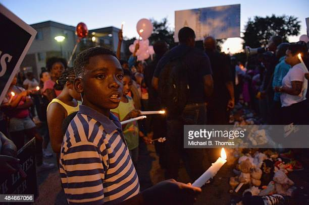 Children gather at the Michael Brown Jr memorial on Canfield Drive during a candlelight vigil held in honor of Jamyla Bolden on August 20 2015 in...