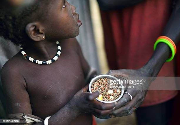 Children gather grain off a field demarcated for food-drops at a village in Nyal, an administrative hub of Panyijar county in Unity state, south...