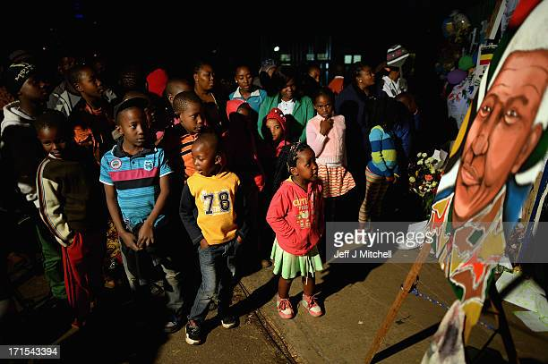 Children gather to leave messages of support for former South African President Nelson Mandela outside the Mediclinic Heart Hospital June 26 2013 in...