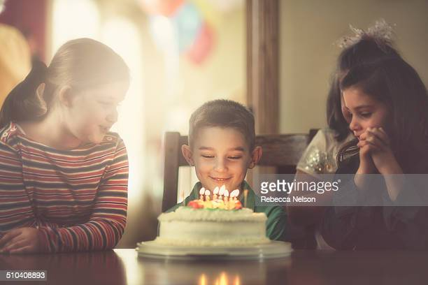 children gathered around boy with birthday cake - rebecca nelson stock pictures, royalty-free photos & images