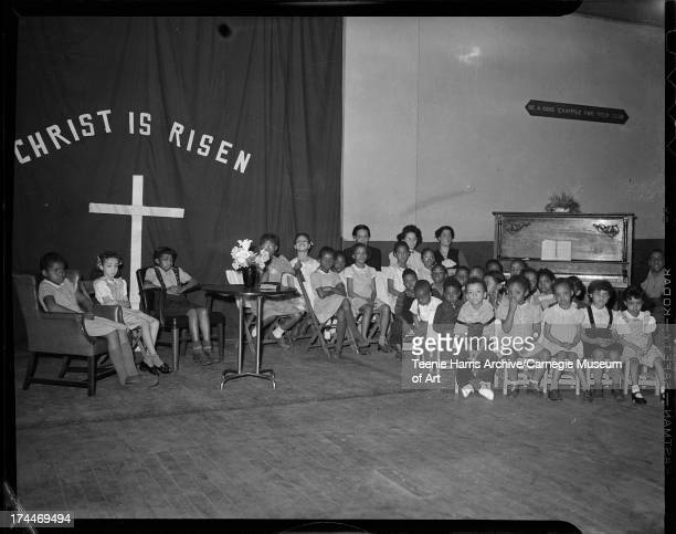 Children gathered in interior with large curtain inscribed 'Christ is risen' and wall inscribed 'Be a good example for your club' for Easter program...