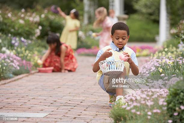 children gathering easter eggs in garden - chasse aux oeufs de paques photos et images de collection