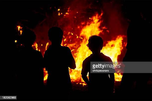 Children gazing at a raging bonfire in the dark