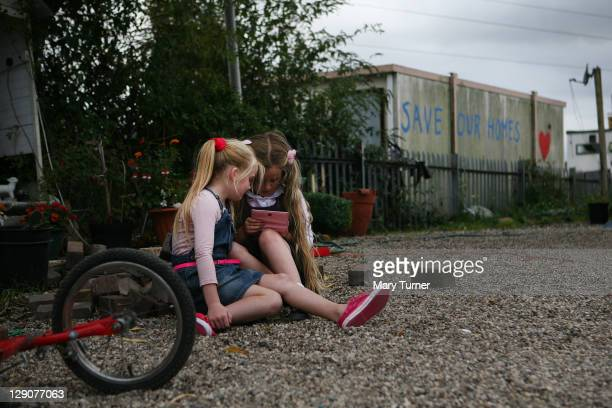 Children Georgina Flynn and MaryAnn McCarthy sit beside a 'Save Our Homes' sign at the Dale Farm Traveller site on October 12 near Basildon England...