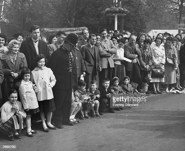 Children get a front line pavement seat to watch Princess Margaret's wedding procession pass.